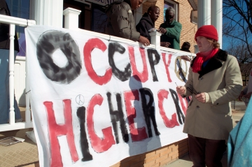 Tim Franzen putting up Occupy Higher Ground sign