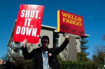 Daniel Hanley, Occupy Atlanta, holding sign in front of Wells Fargo