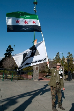 Veteran John Ahearn II holding Peace sign with Syrian Freedom sign